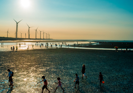 Wind farm on a beach with lots of visitors